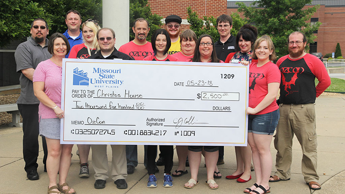 OzCon committee members and Christos House personnel pose with check