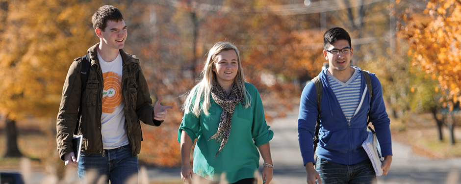 Three students walking across campus in the autumn sunshine.