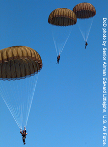 Military personnel in parachutes floating to the ground.